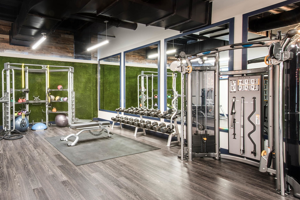 Weight lifting equipment in a wood floored fitness center