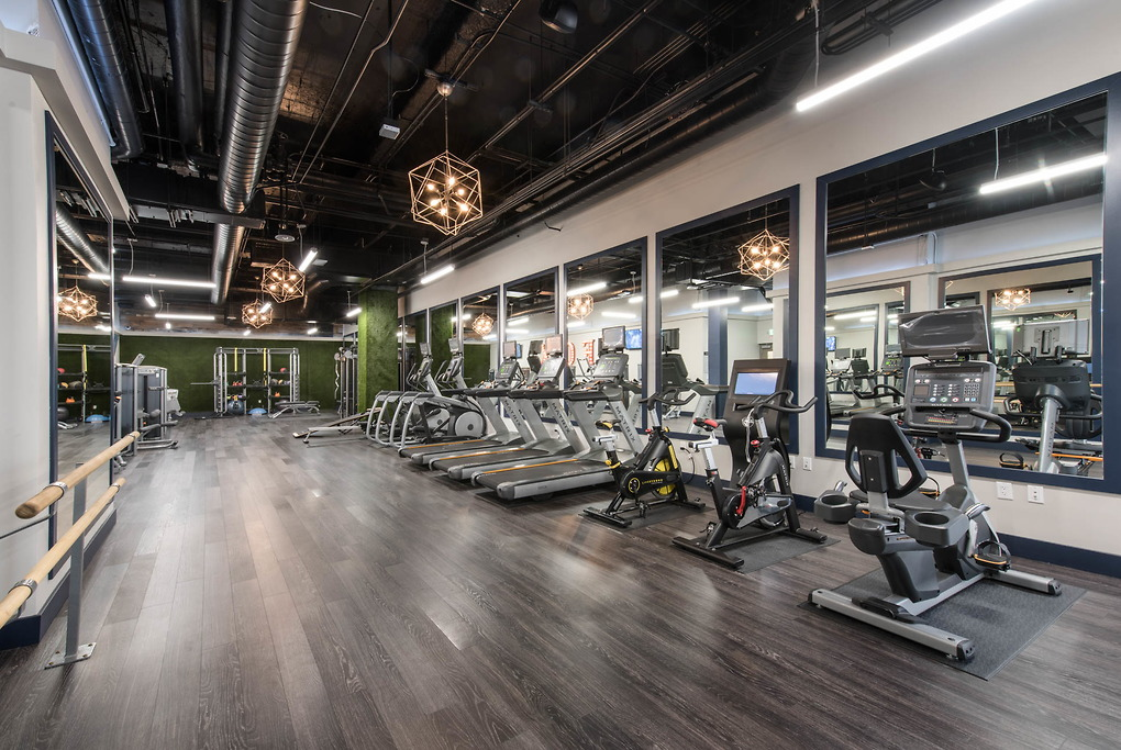 Custom lighting above a fitness center with green walls